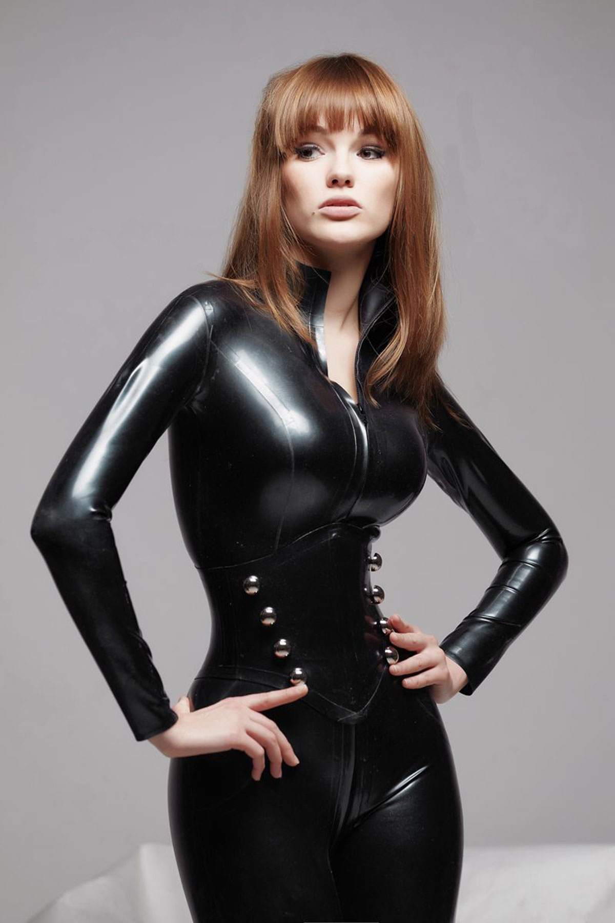 Beautiful blonde vamp mistress in black fetish corset on white home background stock image